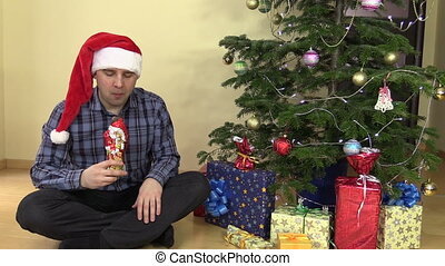 Man with red hat eat Santa form chocolate with satisfaction