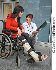 Woman with leg in plaster, doctor and chair - Young woman...
