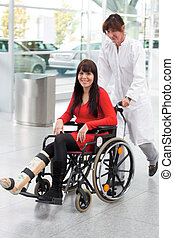 Woman with leg in plaster, wheelchair and nurse