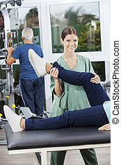 Nurse Assisting Woman In Leg Exercise At Rehab Fitness...