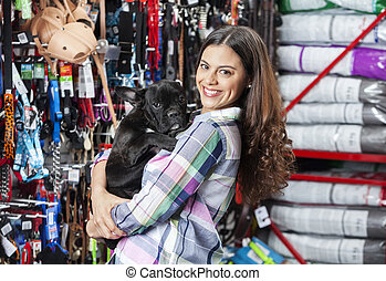 Portrait Of Woman Carrying French Bulldog At Store - Side...