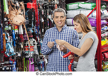 Couple Buying Sausage Toy In Pet Store - Portrait of happy...