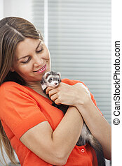 Happy Woman Embracing Weasel - Happy mid adult woman...