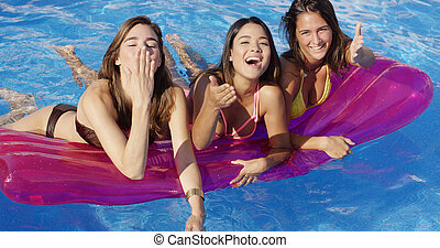 Three bikini clad beauties on a floating device