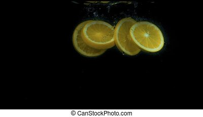 Oranges falling into water in slow motion on black background