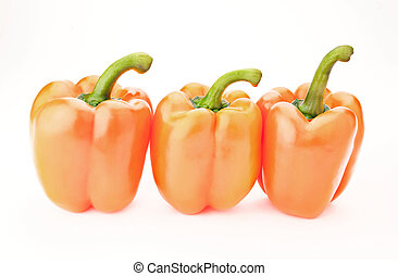 Fresh vitamin background - three orange peppers over white