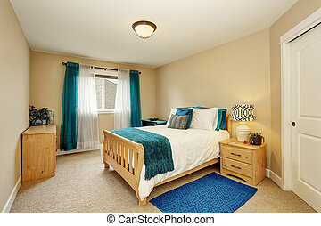 Neat beige bedroom with turquoise curtain and wooden bed....