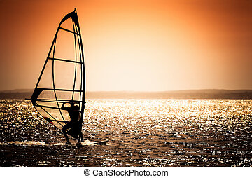 sunset and surf - windsurfer silhouette against a sunset...