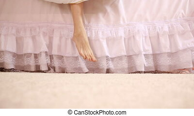 Woman legs with soft skin in the bedroom. woman gets out of bed