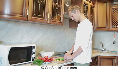 Smiling man preparing salad in the kitchen