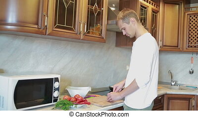 wife hugging her husband while he cutting vegetables for...