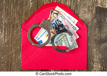Red Envelope with Euro bills and handcuffs over wooden...