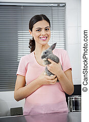 Beautiful Mid Adult Woman Holding Ill Rabbit - Portrait of...
