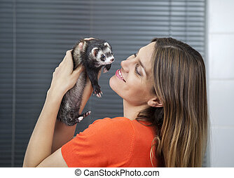 Happy Woman Playing With Weasel In Veterinary - Happy mid...