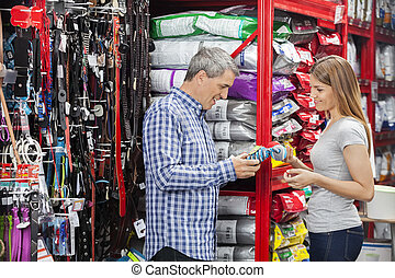 Smiling Couple Buying Toy In Pet Store - Side view of...
