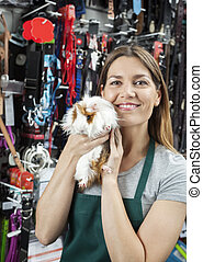Saleswoman Holding Cute Guinea Pig At Store - Portrait of...