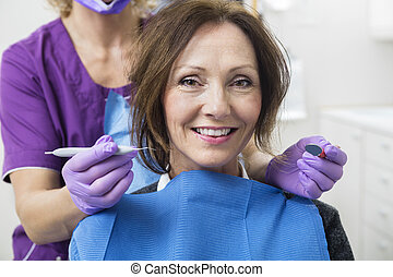 Happy Female Patient With Dentist Holding Tools - Portrait...