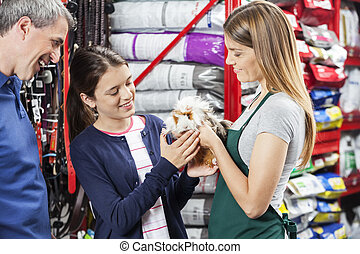 Saleswoman Giving Guinea Pig To Girl At Store - Smiling...