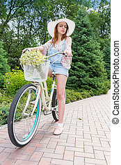 Fabulous attractive woman wearing a white hat sitting on her...