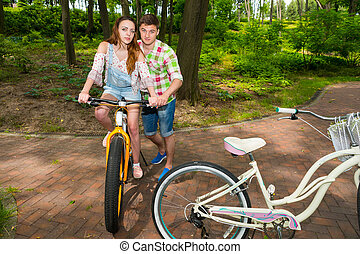 Handsome male teaches his girlfriend riding a bicycle in a...