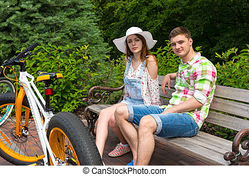 Young fashionable couple sitting on bench near bikes in park...