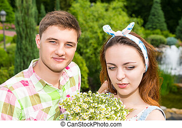 Young couple with bouquet flowers having a date outside -...