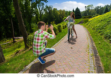 Man taking a photo of his girfriend sitting on a bike - Man...