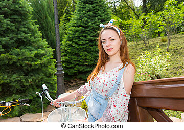 Young romantic female standing near her bicycle and smiling...