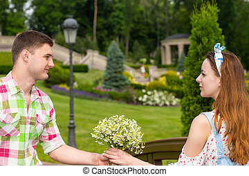 Young man gives a girl flowers on footbridge in park - Young...