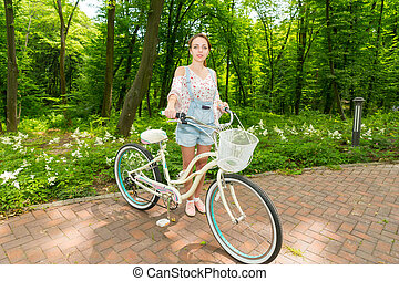 Young happy girl with her bicycle standing on bricks in a...