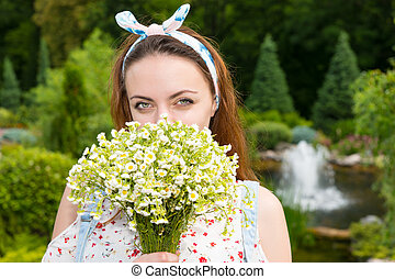 Romantic beautiful young woman smelling flowers outside -...