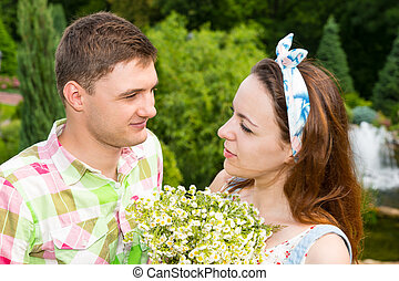 Young couple with bouquet flowers looking at each other -...