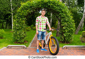 Handsome male with bike in a park - Handsome male standing...