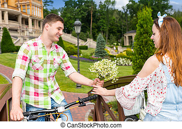 Young man gives a girl flowers while they are riding on...