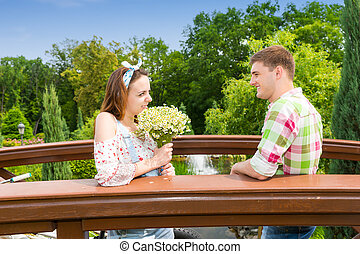 Happy young couple having a date on a bridge in the park -...