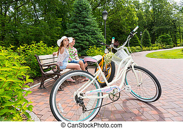 Romantic couple sitting on bench near bikes parked on brick...