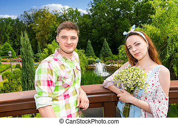 Beautiful young couple having a date on a bridge in the park...