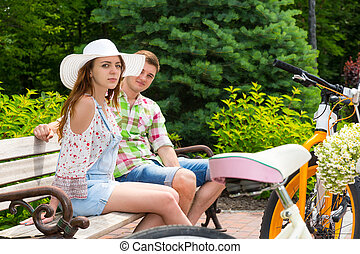 Attractive young couple sitting on bench near bikes in park...