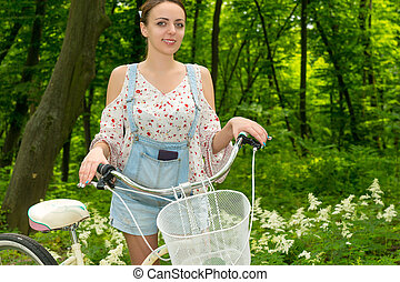 Portrait of smiling girl with her bicycle in a park -...