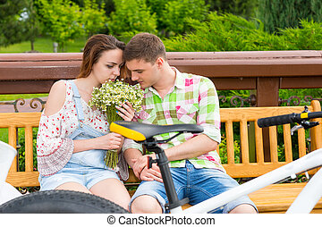 Romantic couple sitting on a bench and smelling flowers in a...