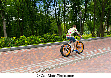 Male riding a bike on a footpath in a park - Male in green...