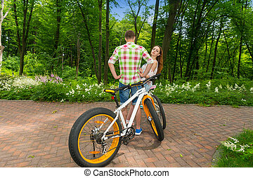 Young female looks out from a guy after biking in a park -...