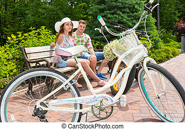 Young attractive male and female sitting on bench near bikes...