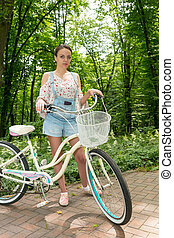 Young female with her bicycle standing on a footpath in a...
