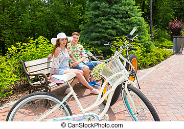 Young male and female sitting on bench near bikes parked on...