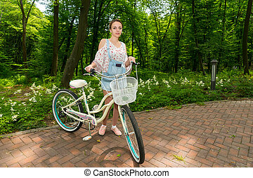 Smiling girl with her bicycle standing on bricks in a park -...