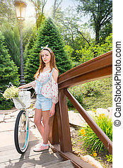 Female standing near her bicycle and smiling - Female...