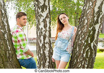 Young male and female leaning on trees in a park - Young...