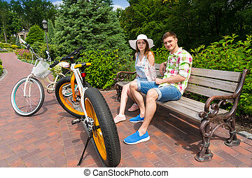 Couple sitting on bench near bikes in beautiful green park -...