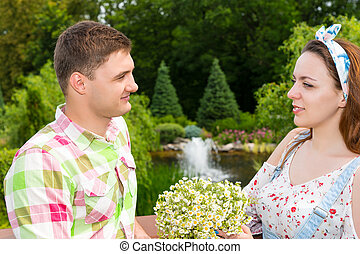Woman holding flowers while cute man looks at her - Young...